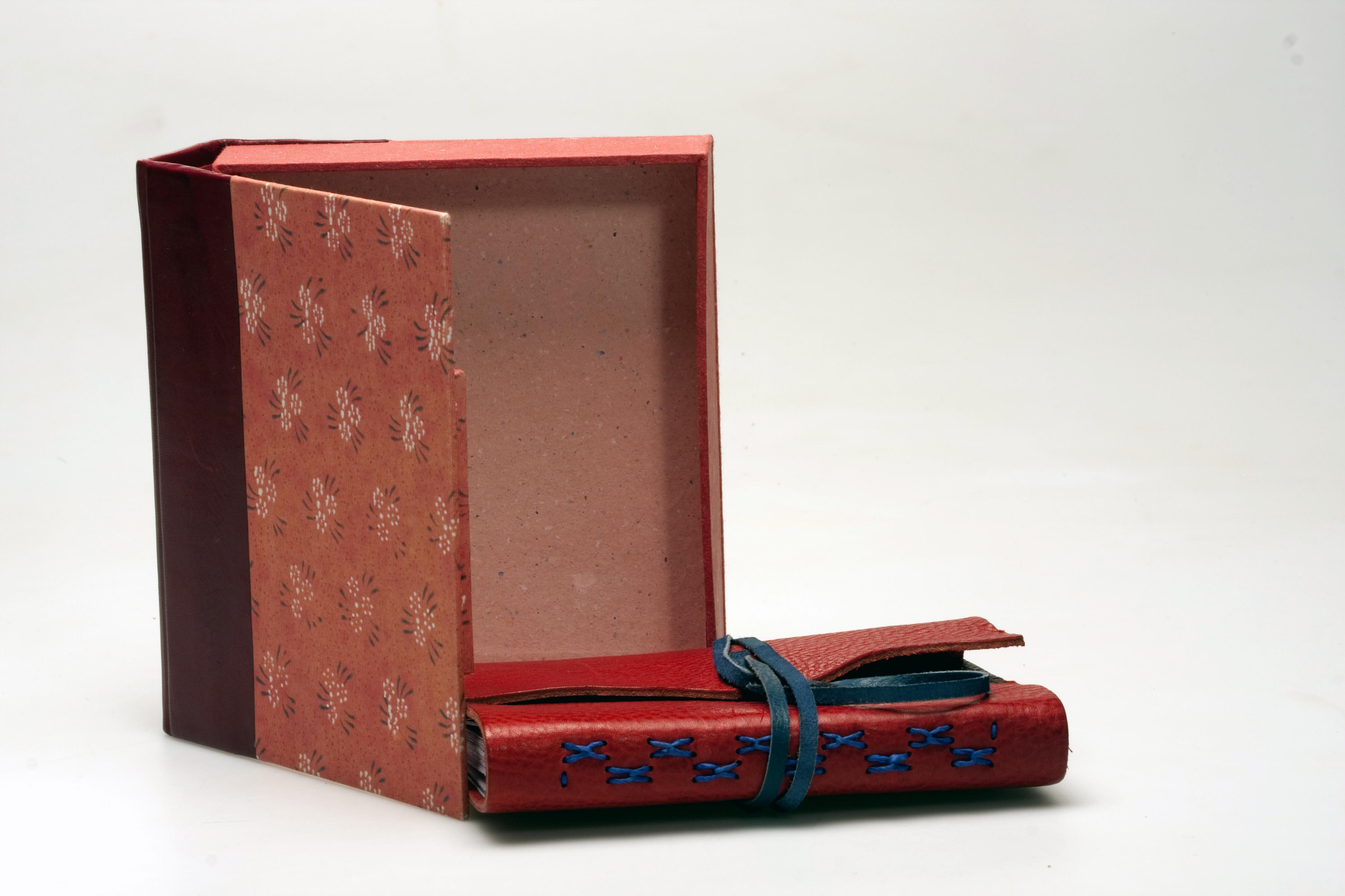 Cuaderno con caja cuero rojo.