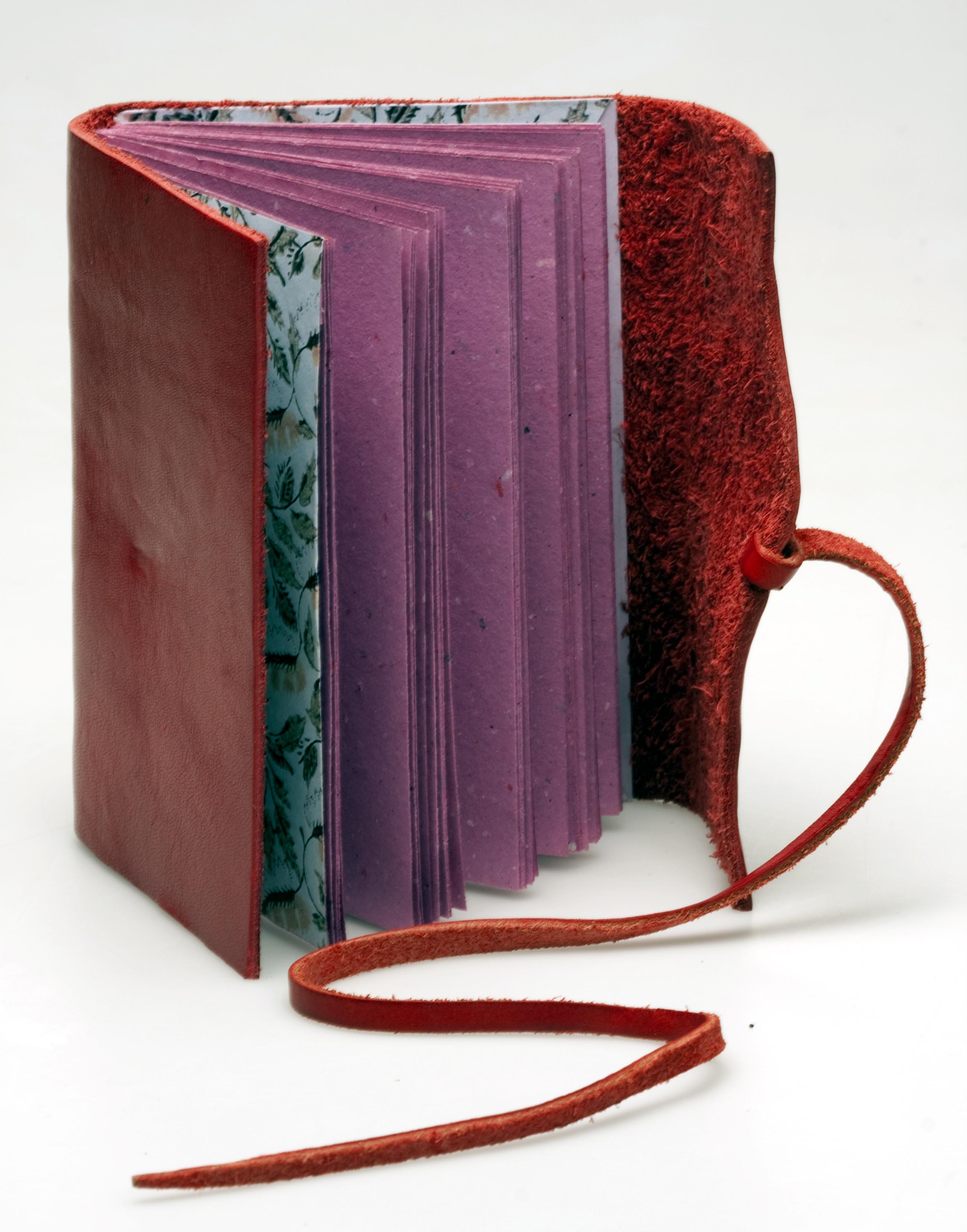 Cuaderno cuero rojo.